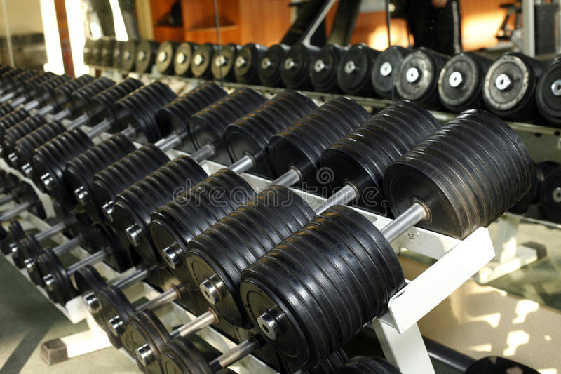 Many dumbells in gym. Health club many dumbells in gym stock photography