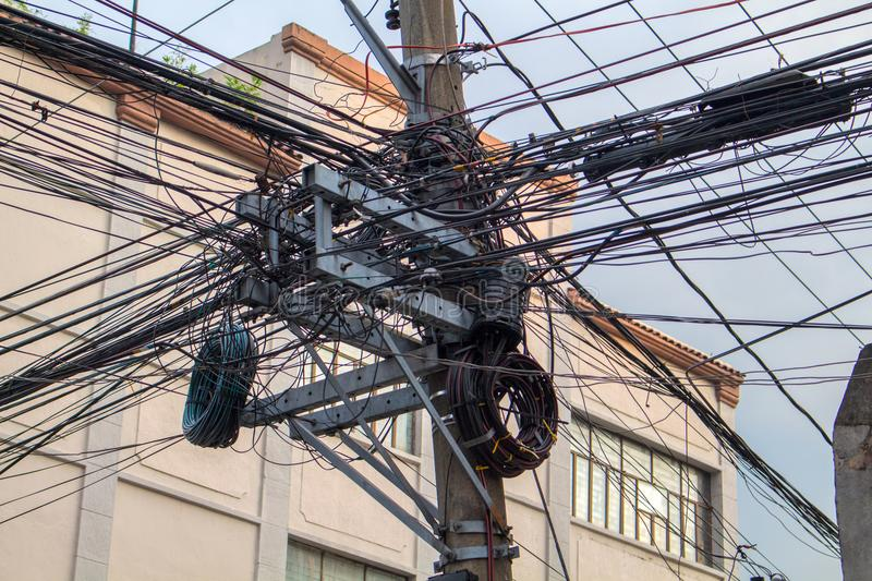 Many electrical wires on pillar. Asian urban electric supply. Industrial electrification pole with wire mess. stock photos