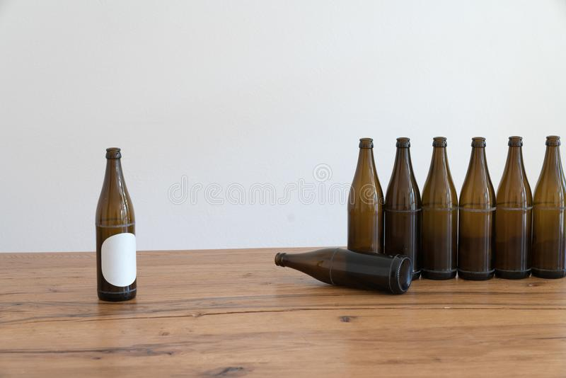 Many empty brown beer bottles on a wooden table royalty free stock images