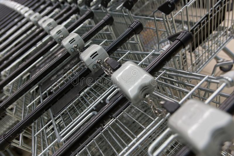 Many empty shopping carts in a row. Inside a large supermarket. Fastened with a chain. Paid usage stock photos