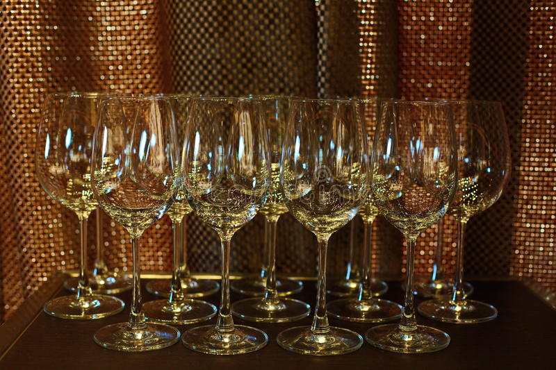 Many Empty Wine Glass in order on table and copper back light as royalty free stock images