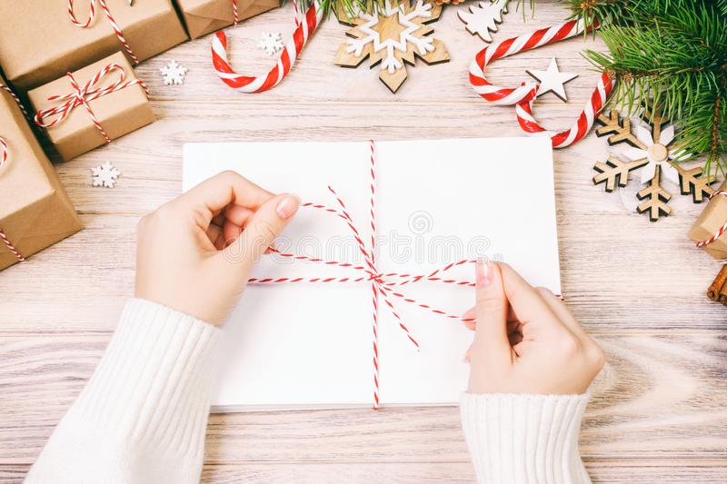 Many envelopes tied with rope. Close-up top view of famale hands with envelope. Pine cones and christmas decoration on old wooden royalty free stock photography
