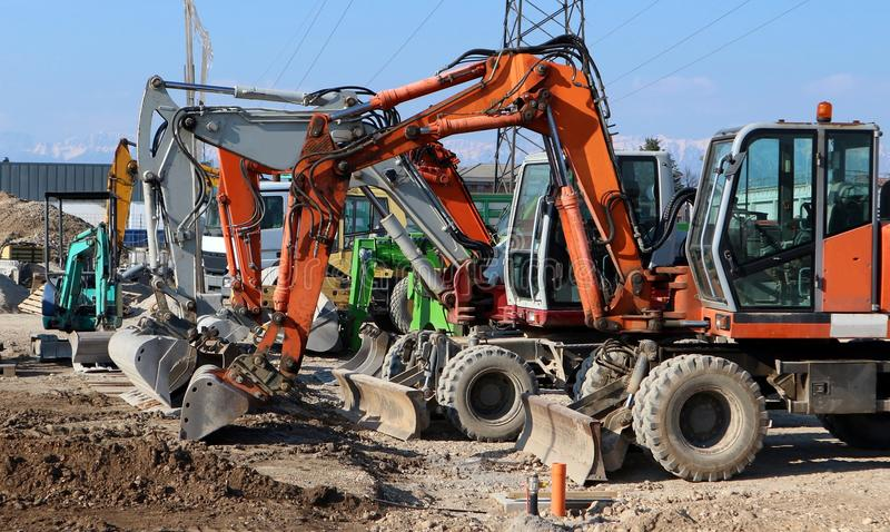 Many excavators of different colors and sizes lined up at the construction site, waiting to get back to work royalty free stock photo