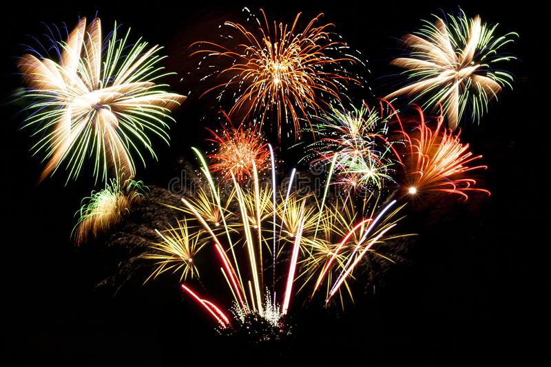 Many firework explosions in the sky. Big firework display with multiple fireworks in the dark black sky royalty free stock photos