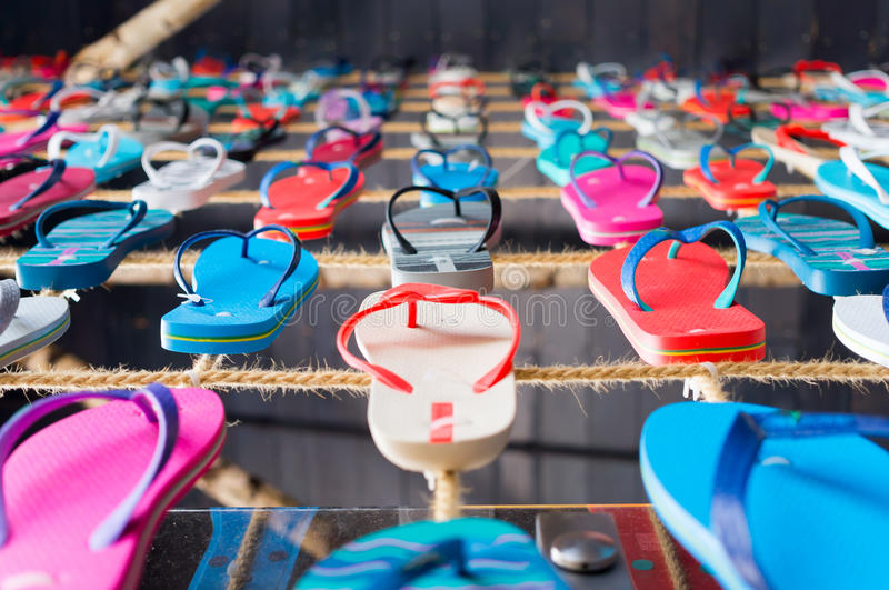 Many flip flop sandals aligned on a string. Photo of many flip flop sandals aligned on a string part of a wall deco in a Romanian seaside terrace stock photos