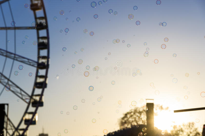 Many Floating Bubbles in Winter Wonderland. Many floating bubbles with a blurred background of giant wheel against a sunset sky stock photo