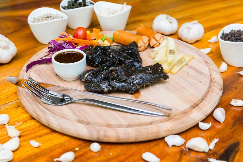 Many food on table. Steak black chicken on wood dish royalty free stock images
