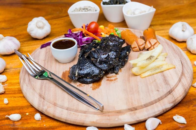 Many food on table. Steak black chicken on wood dish stock image