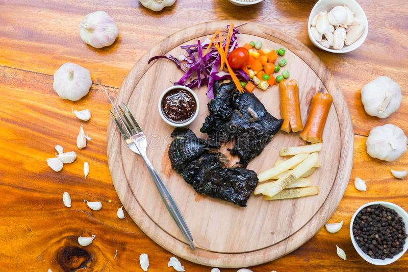 Many food on table. Steak black chicken on wood dish stock photo