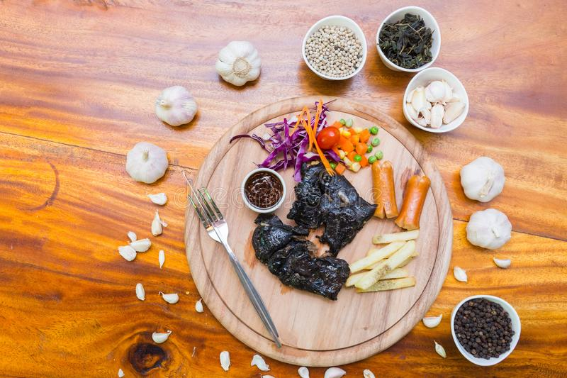 Many food on table. Steak black chicken on wood dish stock images