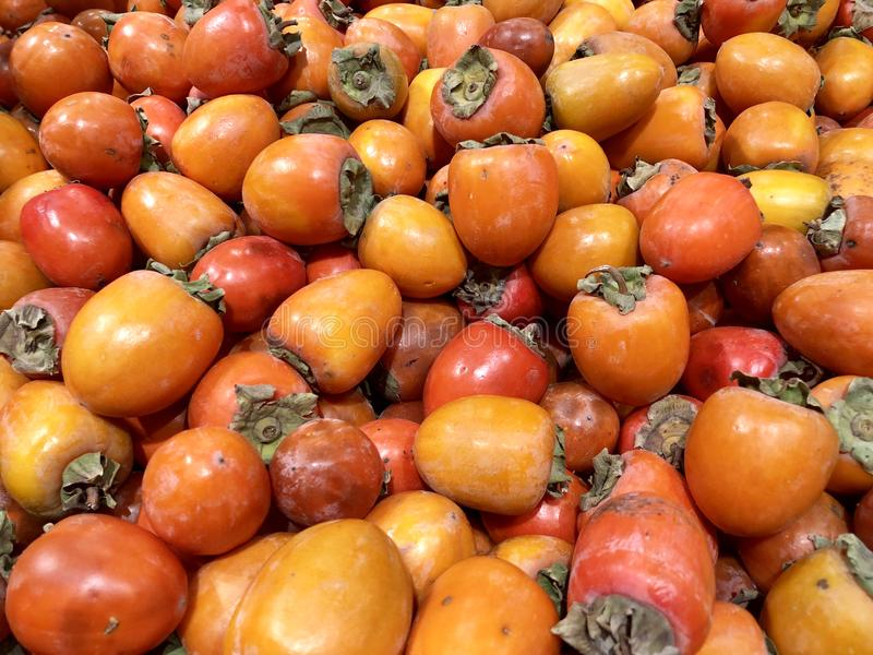 Many fresh fruits persimmons in supermarket, food concept background stock image