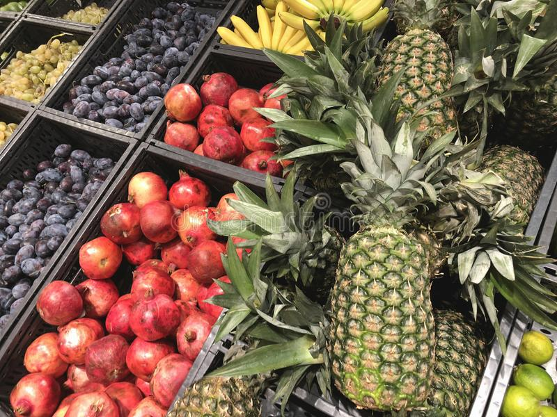 Many fresh fruits in supermarket, pineapples, pomegranate, plums, food concept stock images