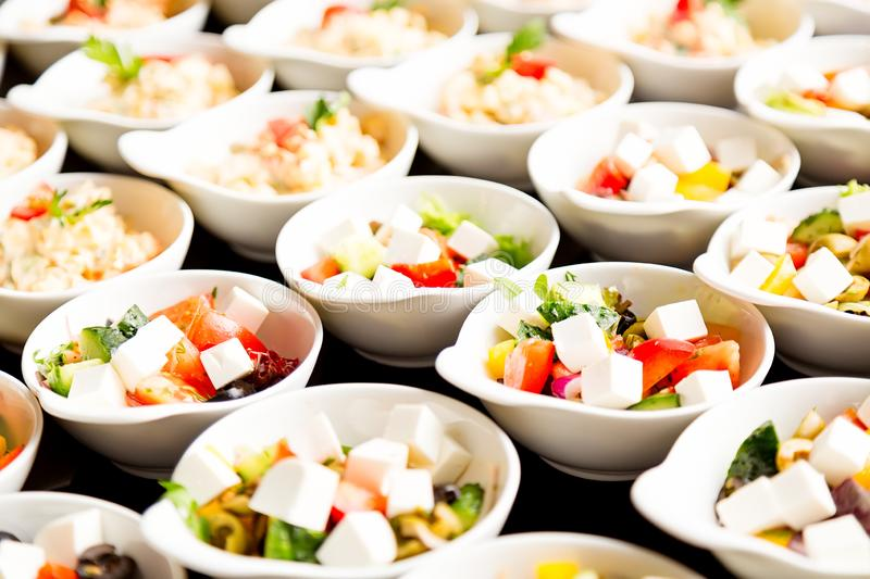 Many fresh greek salad plates. Close up with selective focus royalty free stock images