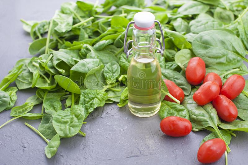 Many Fresh spinach leaves, vegetable oil in a bottle and small cherry tomatoes. Vitamins and health. Free space for text. Copy royalty free stock photography