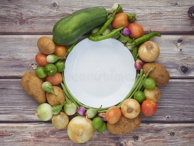 Many fresh vegetables are placed on a wooden table stock image