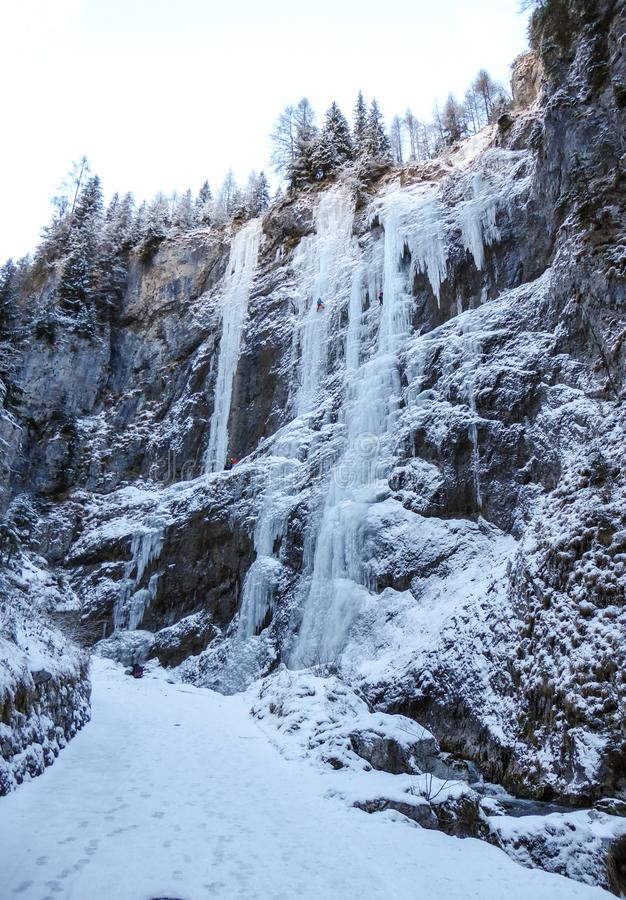 Many frozen waterfalls with extreme ice climbers on them on a cold winter day in the Dolomites in Italy. Near Sottoguda royalty free stock photo
