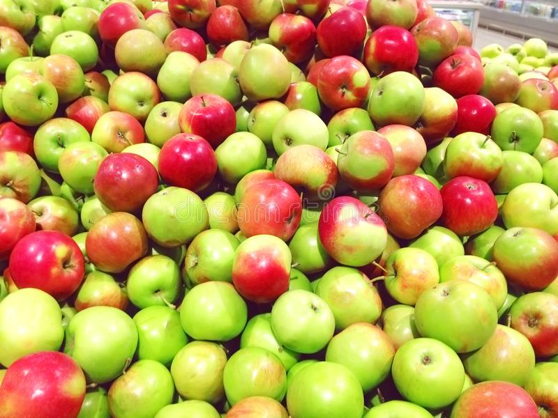 Many fruits green, red apples lying at supermarket close up royalty free stock photo