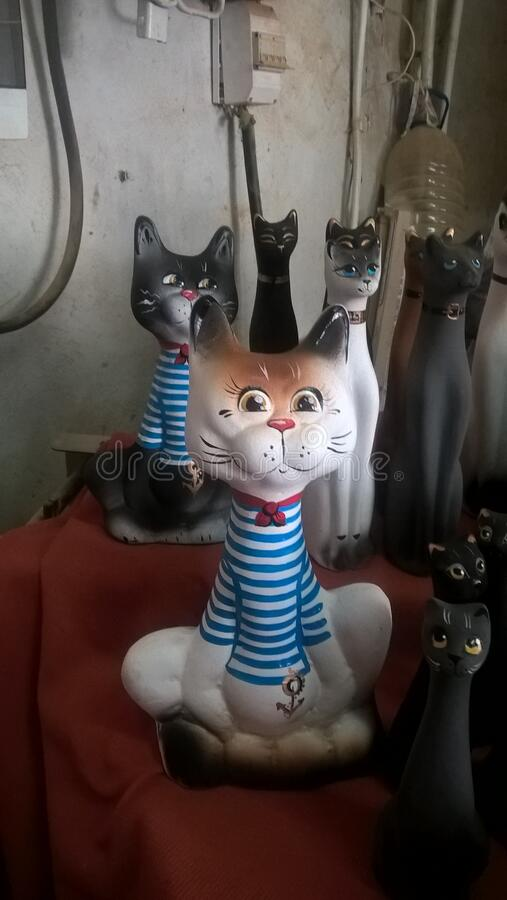 Funny cats and cats made of clay. Collection of cats made in Rostov. Cat Matroskin, from the ship in sea clothes. Many funny cats and cats made of clay stock photo