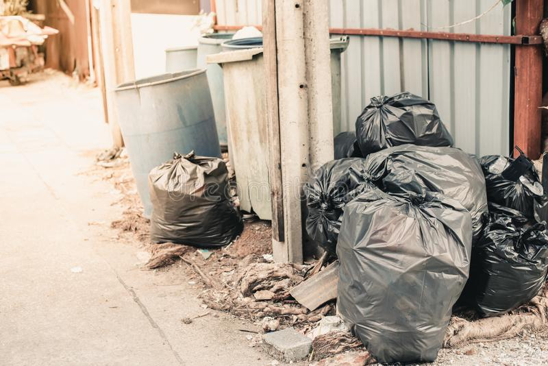 Garbage plastic bags black waste, pollution, lots junk dump, recycle green yellow bin. Many garbage plastic bags black waste, pollution, lots junk dump, recycle royalty free stock image