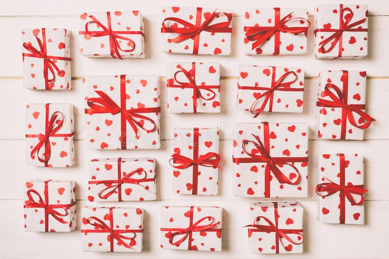 Many gift boxes with red ribbon and heart. valentine or other holidays concept. top view toned on wooden background royalty free stock photography