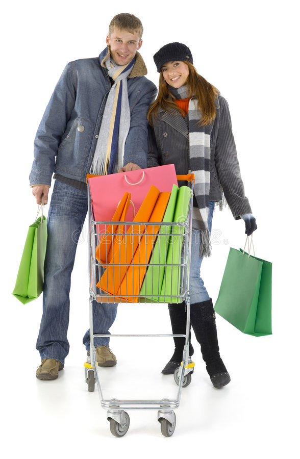Many gifts. Young couple with full trolley. Smiling and looking at camera. Isolated on white in studio. Whole body, front view royalty free stock image