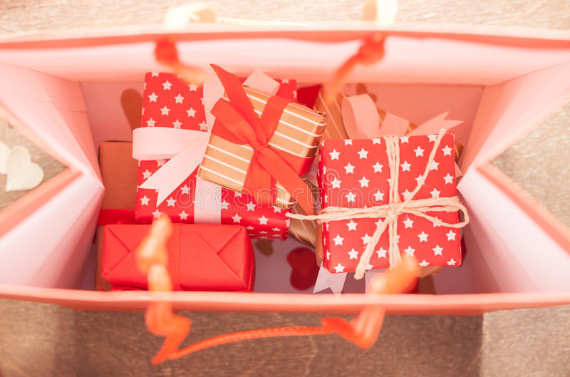Many gifts in bag. Many red christmas gifts inside paper bag stock photo