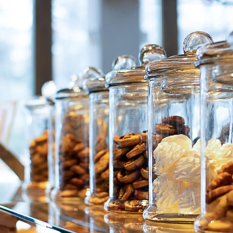 Many glass jars with caps filled with cookies and sweets, on defocused background with reflection. Jars contain marsh-mallow and royalty free stock photos