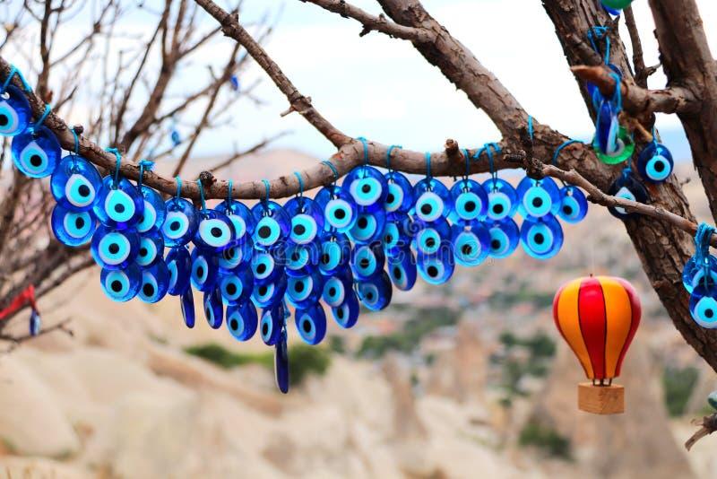 Evil eye charms hang from a tree in Cappadocia, Anatolia, Turkey. Many glass mascots - evil eye charms hang from a tree in Cappadocia, Pigeon valley, Anatolia stock photography