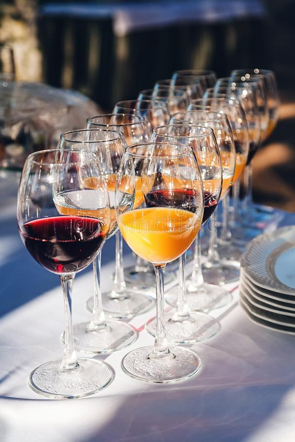 Many glasses of juice, wine and water stand royalty free stock photography