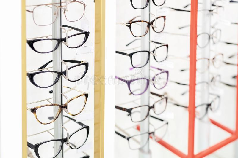 Many glasses rows at optical retail store. Rich assortment choice of different eyewear frames on eyeglasses shop display royalty free stock image