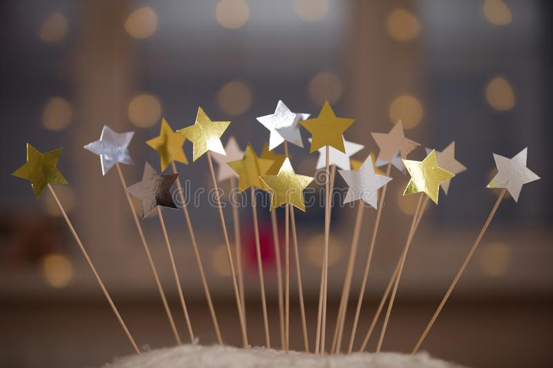 Many golden and silver shiny stars on top of homemade birthday cake. Stars and lights as Christmas or birthday party. Decorations. Cake decor idea. Celebration stock photo