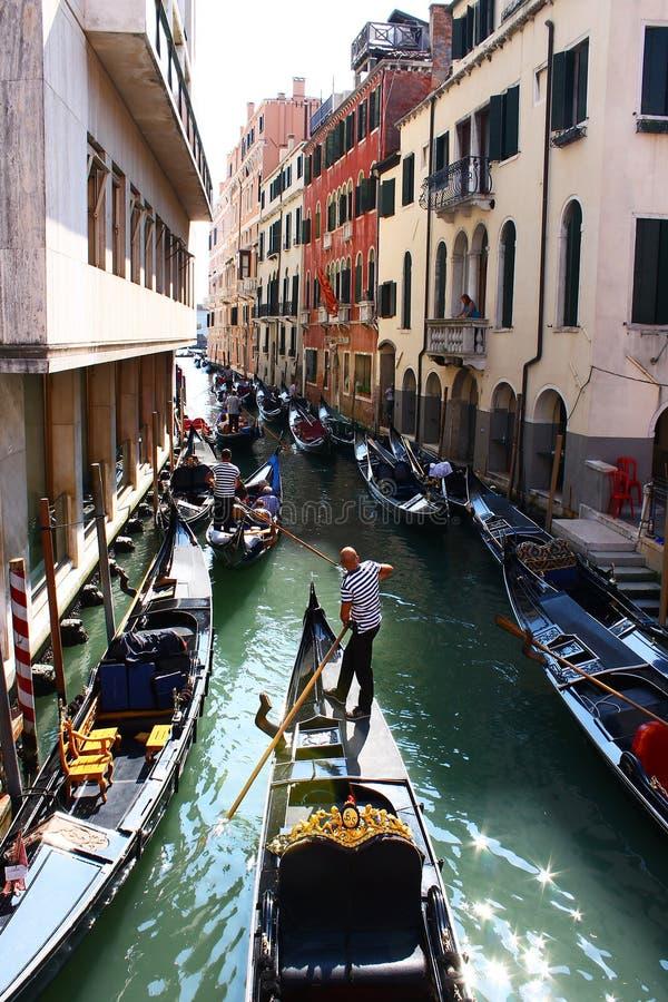 Many gondolas on narrow Venice canal. A lot of gondolas parked on a narrow canal in Venice and a gondolier sailing slowly his famous boat royalty free stock images