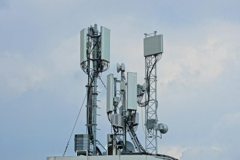 Many gray antennas on the roof of the building. Against the sky royalty free stock photos