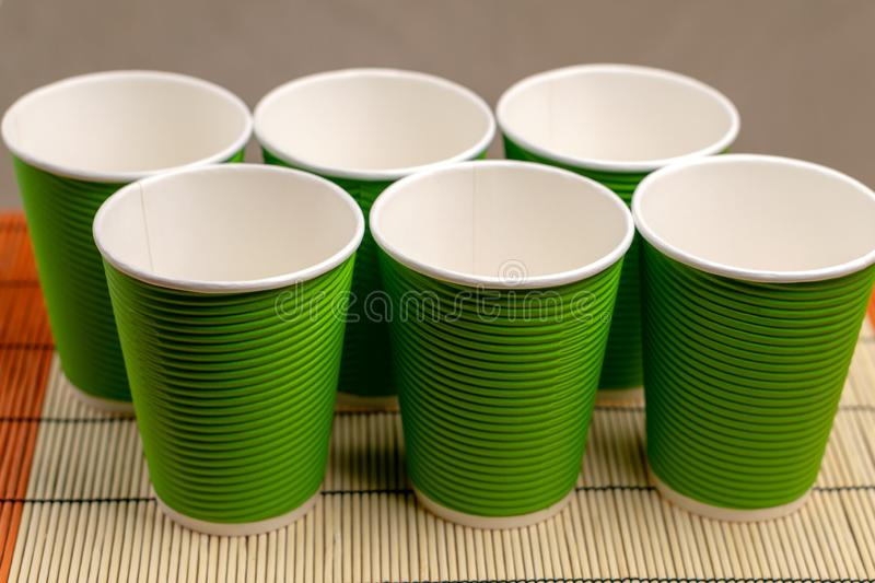 Many green paper cups on a table with bamboo stand.  stock photos