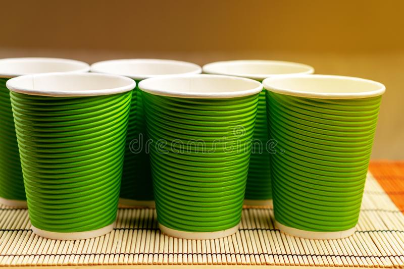 Many green paper cups on a table with bamboo stand.  stock image