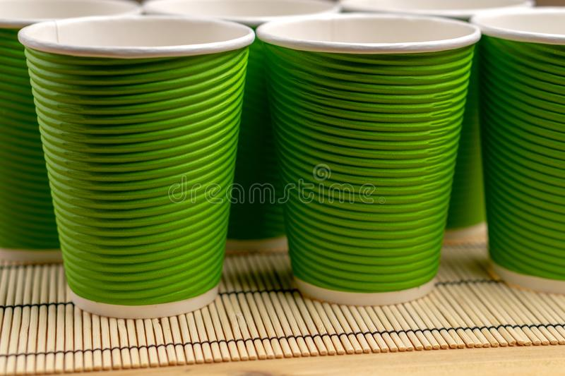 Many green paper cups on a table with a bamboo stand, close-up. Many green paper cups on a table with a bamboo stand royalty free stock images