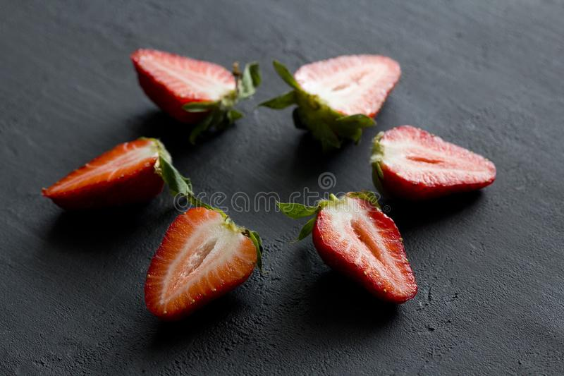 Many Half a strawberry, cut red beautiful strawberry close-up, on a black dark concrete background. Macro shooting. Fruit erotica. Berry fruit mandala, Star stock photos