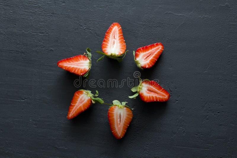 Many Half a strawberry, cut red beautiful strawberry close-up, on a black dark concrete background. Macro shooting. Fruit erotica. Berry fruit mandala, Star stock image