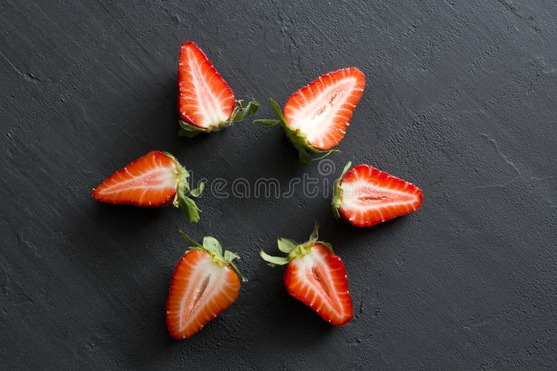 Many Half a strawberry, cut red beautiful strawberry close-up, on a black dark concrete background. Macro shooting. Fruit erotica. Berry fruit mandala, Star royalty free stock images