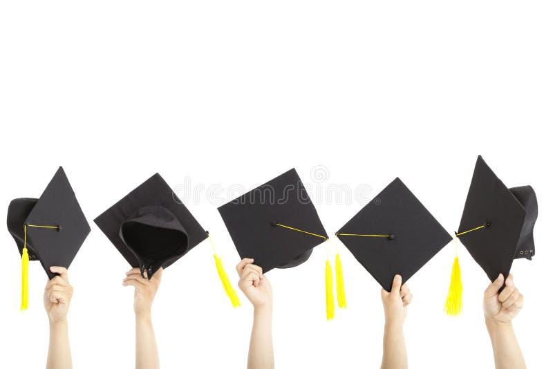 Many hand holding graduation hats stock images
