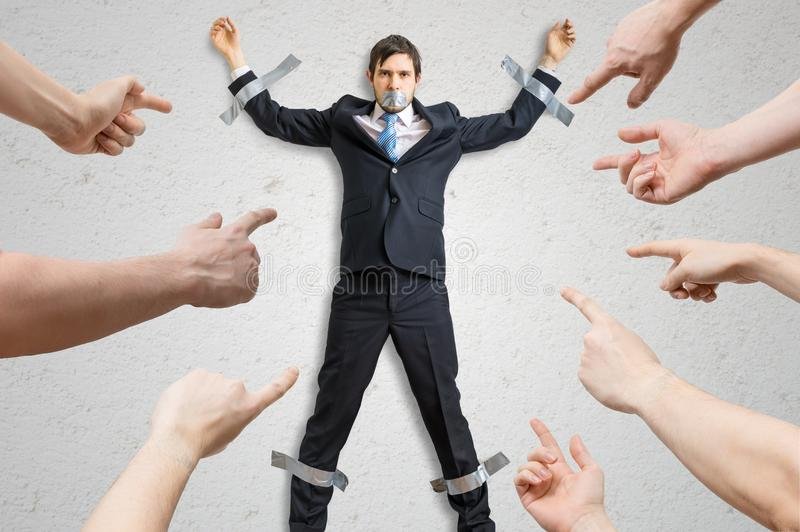 Many hands blame employee who is taped to the wall stock photo