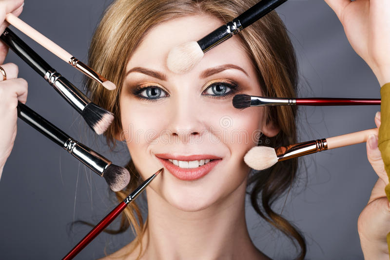 Many hands doing make up to glamour woman. Many hands with cosmetics brushes doing make up to glamour woman stock image