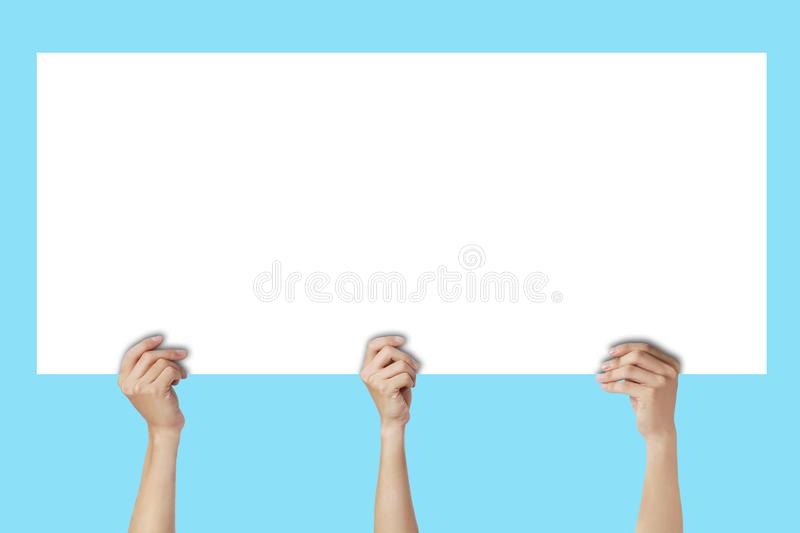 Many hands holding empty space white paper and showing over head. royalty free stock images