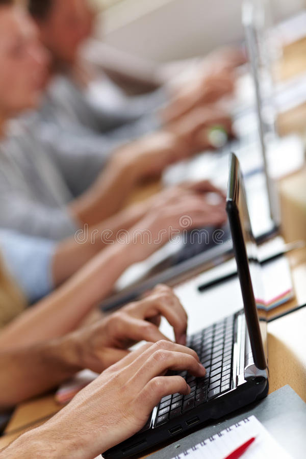 Many hands on laptops stock images