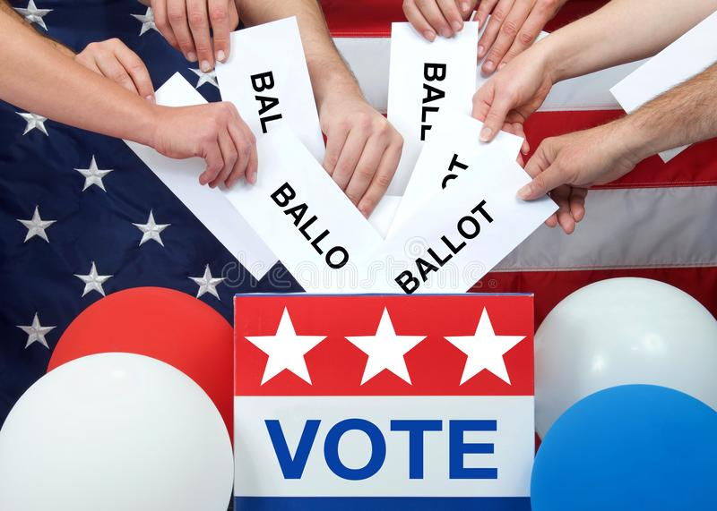 Many hands placing ballots in an election vote box. Hands placing ballots in a voting box, American flag in background. Anyone over the age of 18 on election day royalty free stock photography