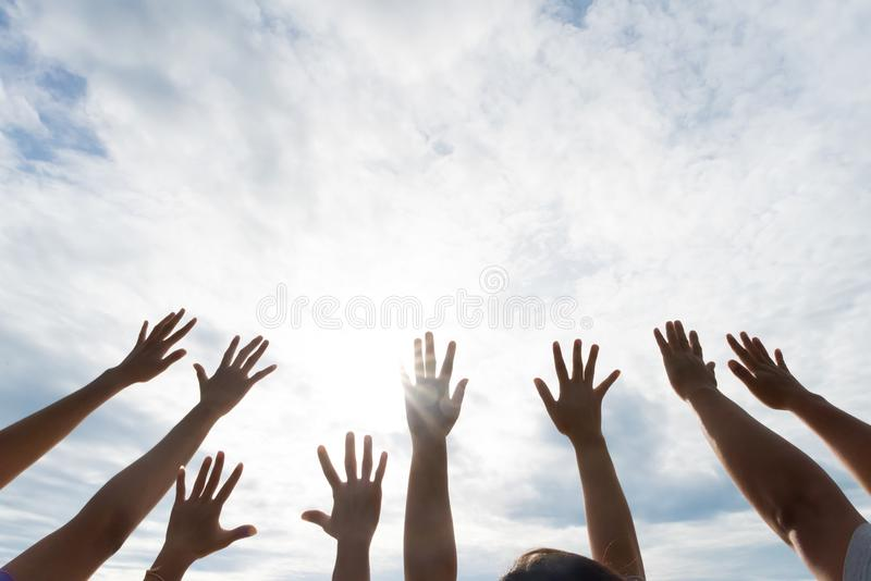 Many hands raised up against the blue sky. Friendship royalty free stock images
