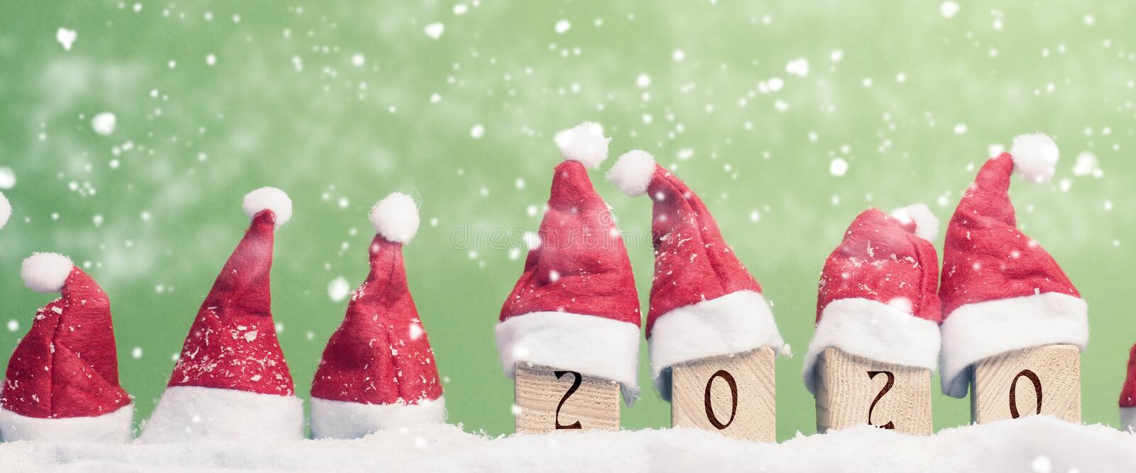 Many hats of Santa in a row with snow. Christmas background, panoramic view royalty free stock photography