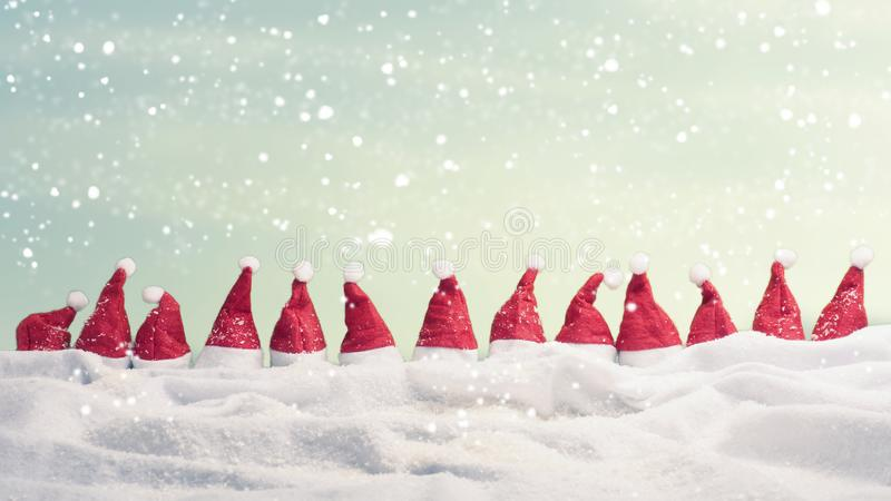 Many hats of Santa in a row with snow. Christmas background, panoramic view royalty free stock photo