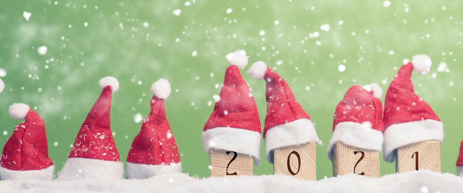 Many hats of Santa in a row with snow royalty free stock photo