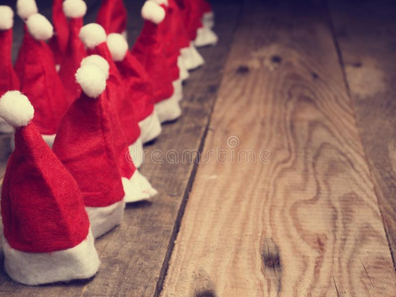 Many hats of Santa on a rustic wooden table. Many hats of Santa in a row on a rustic wooden table with space for text, vintage color stylized stock image
